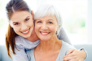 Younger woman and older woman smiling with healthy teeth.