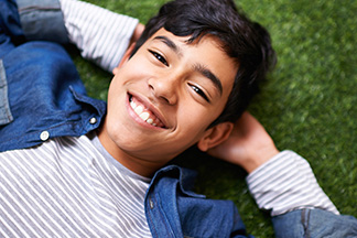 Young teen smiling on grass free of tooth decay.
